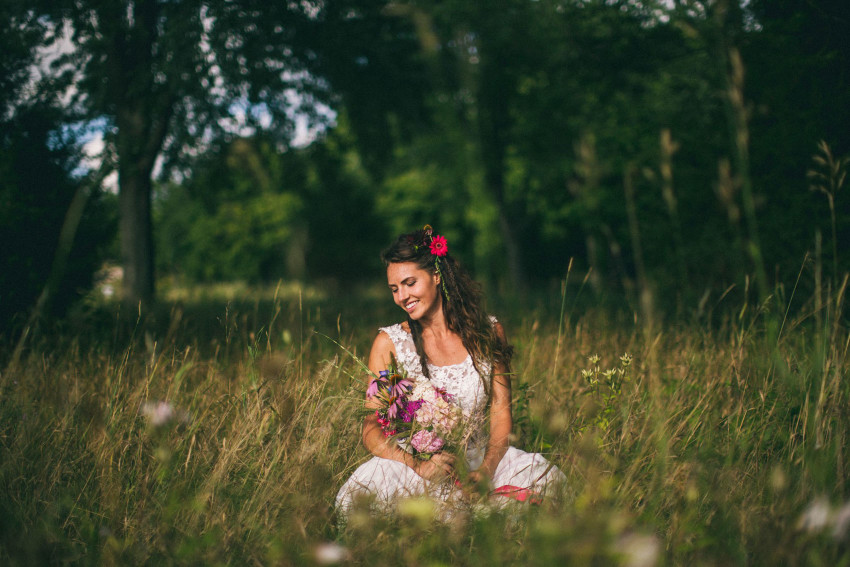 071 Mukwonago Milwaukee WI Barn DIY Laid-back Sweet Bride Sitting On Ground on Wedding Dress Tall Grass Adventurous Danny Andrea
